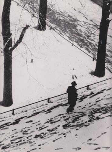 Vintage man walking along in snow on street sidewalk.