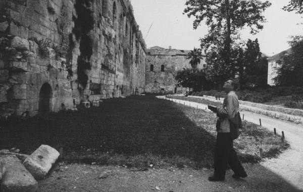 Vintage tourist looking at crumbling wall attraction.