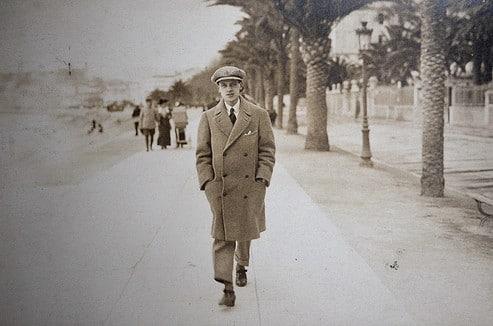 Vintage man walking down sidewalk with overcoat flat cap.