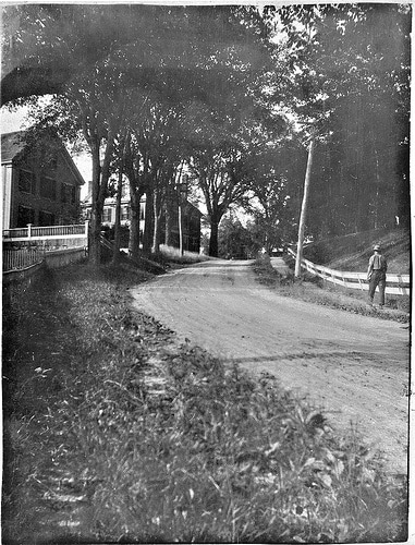 Vintage man walking along dirt road in the country.