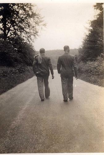 Vintage men friends walking side by side down road.
