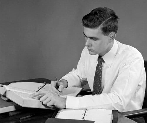 vintage young businessman at desk looking through textbook taking notes
