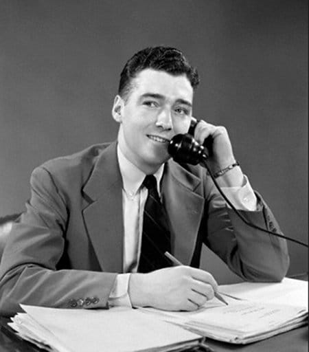 Vintage young businessman at desk with paperwork on phone.