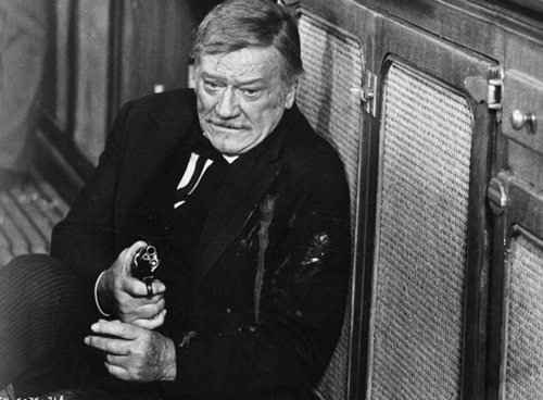 Shootist old western movie film john wayne on ground with gun.