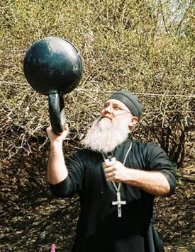 old elderly man priest lifting giant kettlebell