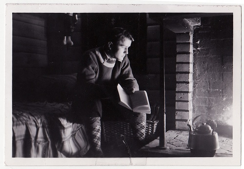 vintage man reading book by a fireplace contemplating