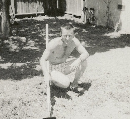 Vintage man with garden hoe working on lawn yard.