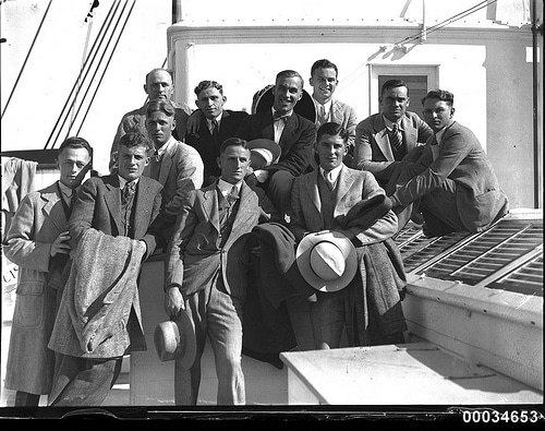 vintage group of men friends in suits on boat