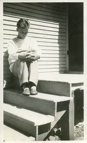 Vintage man reading book on lap on steps of house.