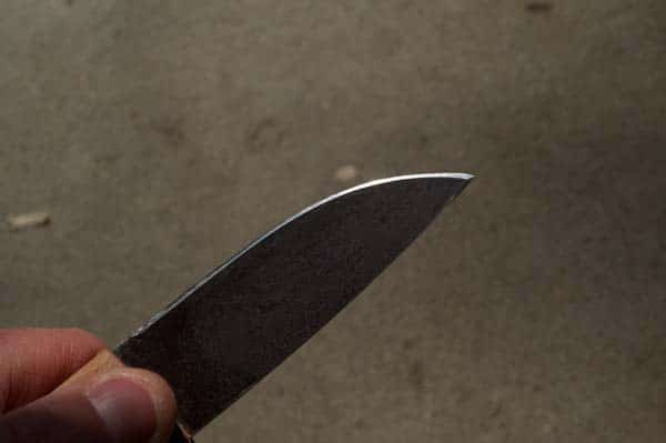 Do a few strokes on one side, then on the other. You'll see your nice flat edge disappear as you remove metal. Watching this edge is a good indicator of how even your filing is. Most people (myself included) tend to screw up the tip by either not filing it enough, or letting the angle drift toward 25…28…30… Be careful and go slow. Stop when you have a filed edge that looks clean and straight.