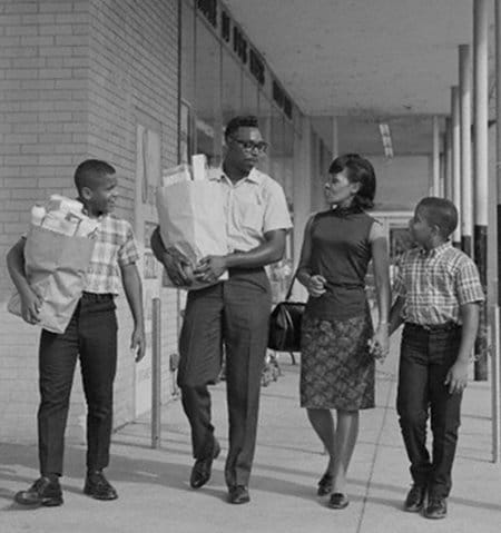 Vintage African American black family walking out of grocery store shopping.