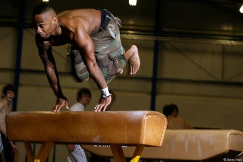 african american black man jumping over pommel horse parkour