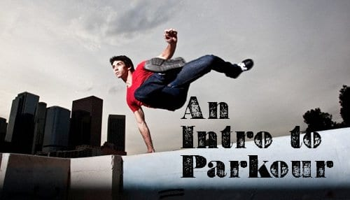 young man jumping over wall parkour