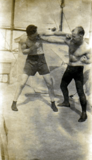 Vintage boxers fighting in ring taking punch.