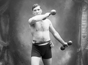 Vintage strongman posing working out with dumbbells.