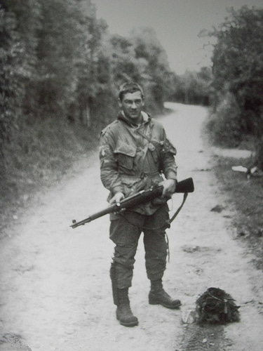 forrest guth wwii soldier holding rifle on dirt road