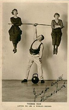 Vintage strongman thomas inch holding up two women.