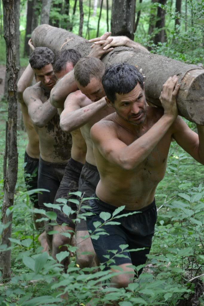 Men in forest carrying log.