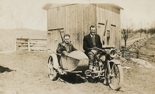 Vintage men on motorcycle with side car.