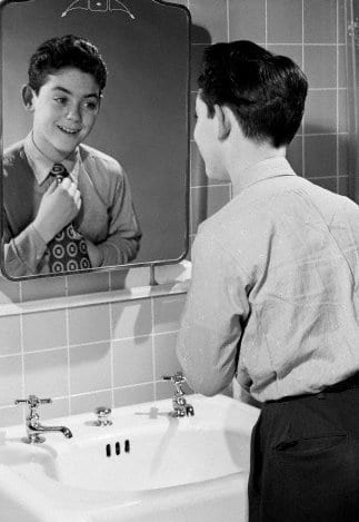 vintage boy adjusting tie necktie in mirror