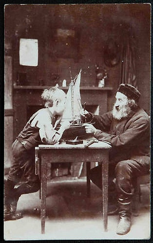 Vintage old man teaching young boy wooden ship model.