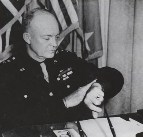 Dwight Ike Eisenhower in military uniform looking at watch.