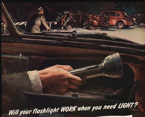 Vintage man sitting in the car and holding flashlight in his hand.