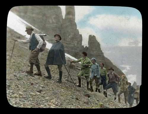 Vintage hiking expedition on mountain men women hiking poles.