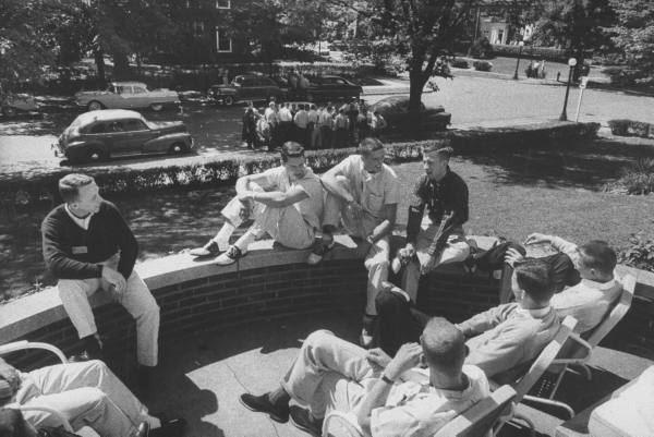 Vintage college students sitting outside talking shooting the breeze.