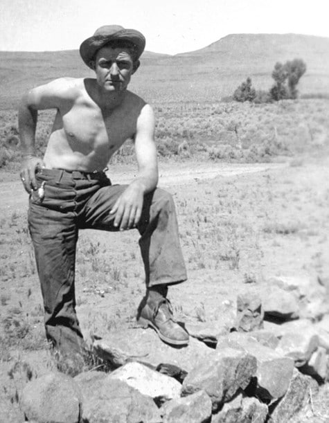 Vintage man leg on rock posing in desert shirt off.