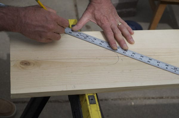 Man using steel ruler on board piece of wood measuring connecting out radius.