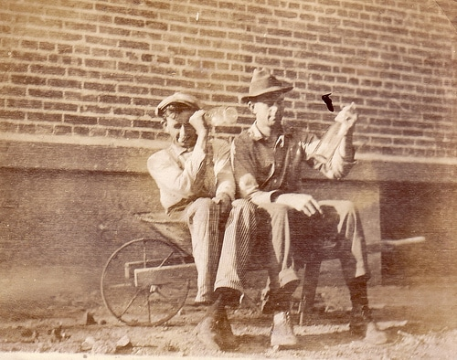 vintage old time photo two men sitting in wheelbarrow with bottles