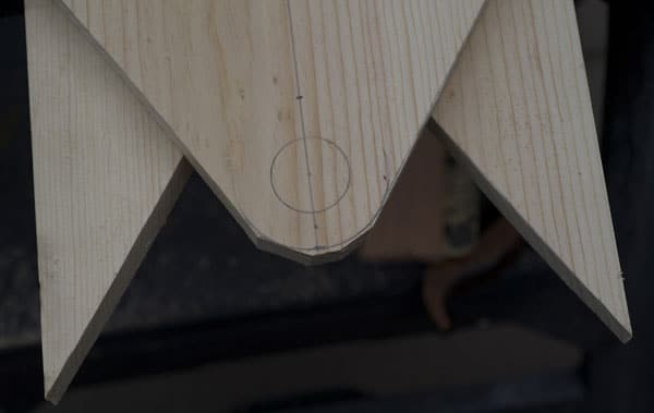 Man using pull saw on piece of wood board end piece rough cut.