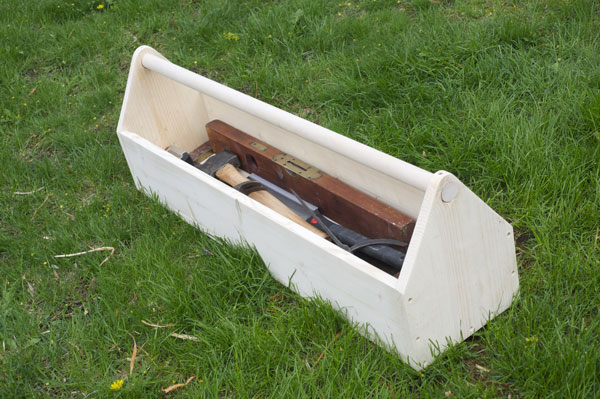 Homemade wooden tool carrier with tools on lawn.