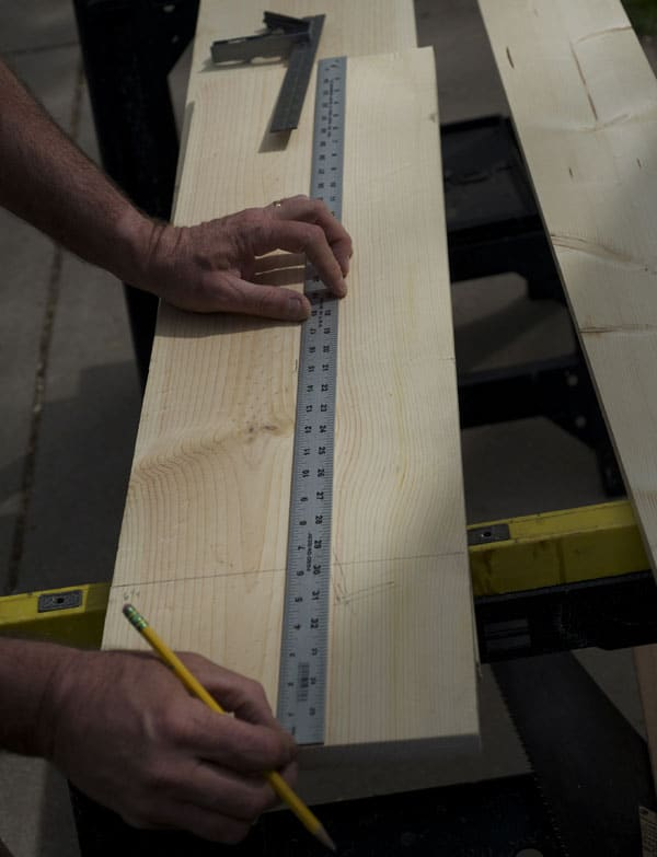 man using steel ruler on board piece of wood measuring