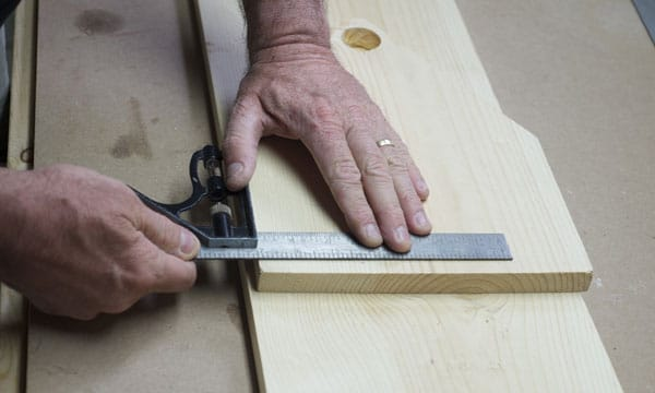Man using steel ruler on board piece of wood measuring.