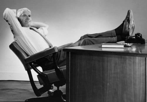 vintage man businessman leaning back in chair feet on desk