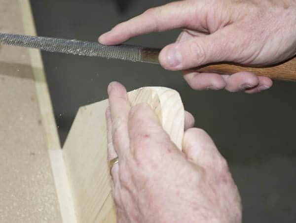 Men using a rasp for clean up the top of the side pieces rasping end.