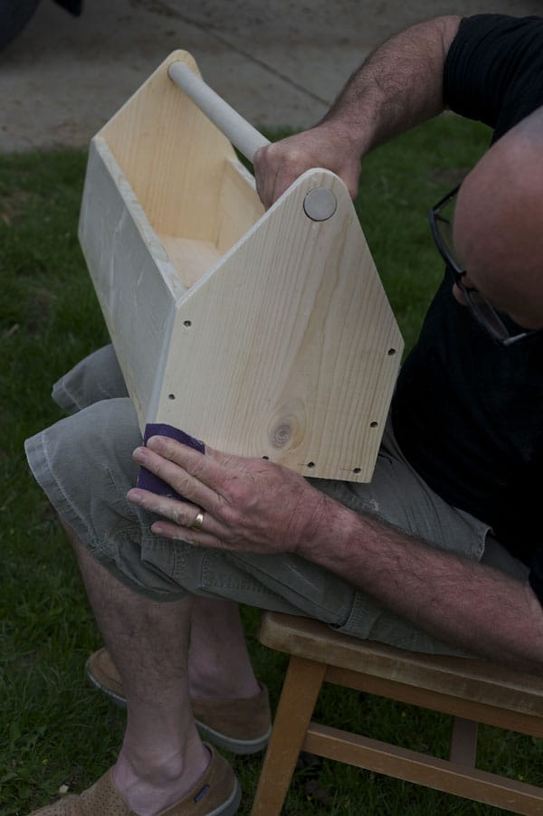 Man using sandpaper at wooden tool box.