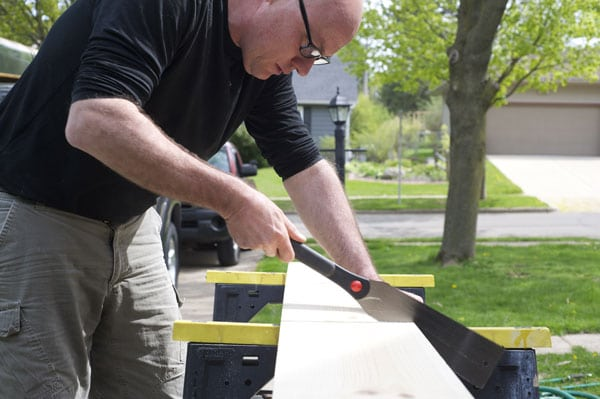 Man sawing board on sawhorses with saw.