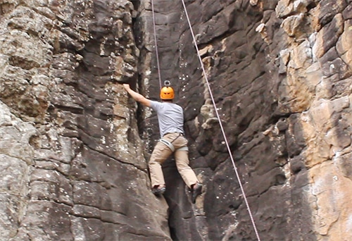 man rock climbing up cliff with ropes helmet