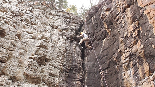 Man rock climbing up cliff with ropes.