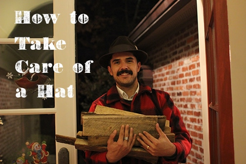 Man in red flannel with firewood wearing fedora.