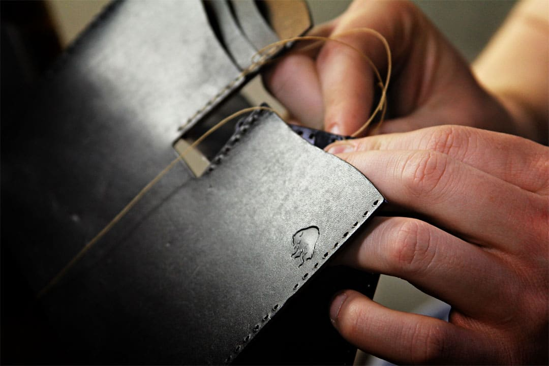 black leather wallet being hand stitched close up photo