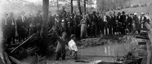 Vintage man being baptized in outdoor pond african american black church.