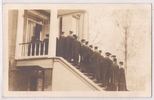 Graduation group men in robes walking up stairs.