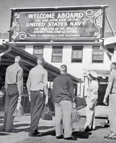 Vintage men looking up at navy sign welcome aboard us navy.