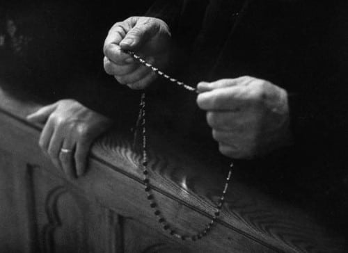 Man holding rosary in hands black white photo close up.