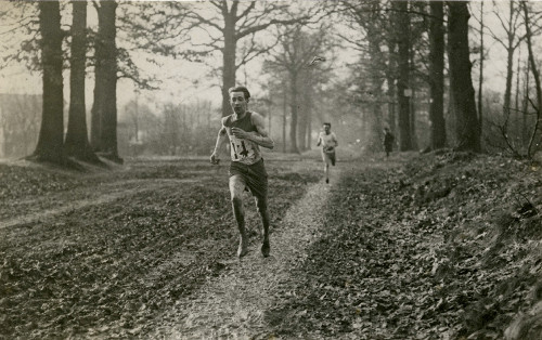 Vintage man trail running through forest woods.