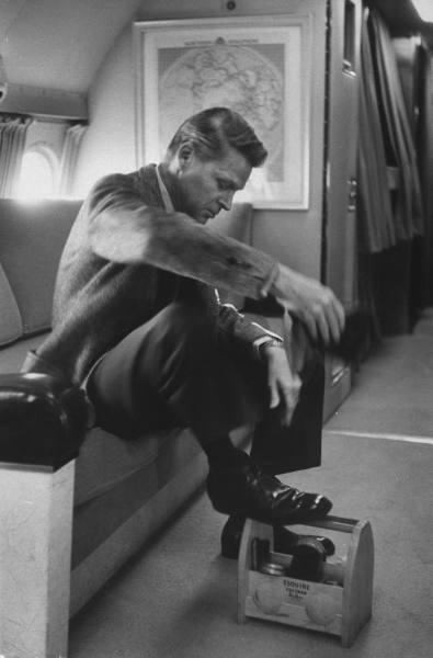 Vintage man on airplane shining shoes on shoe shine box.